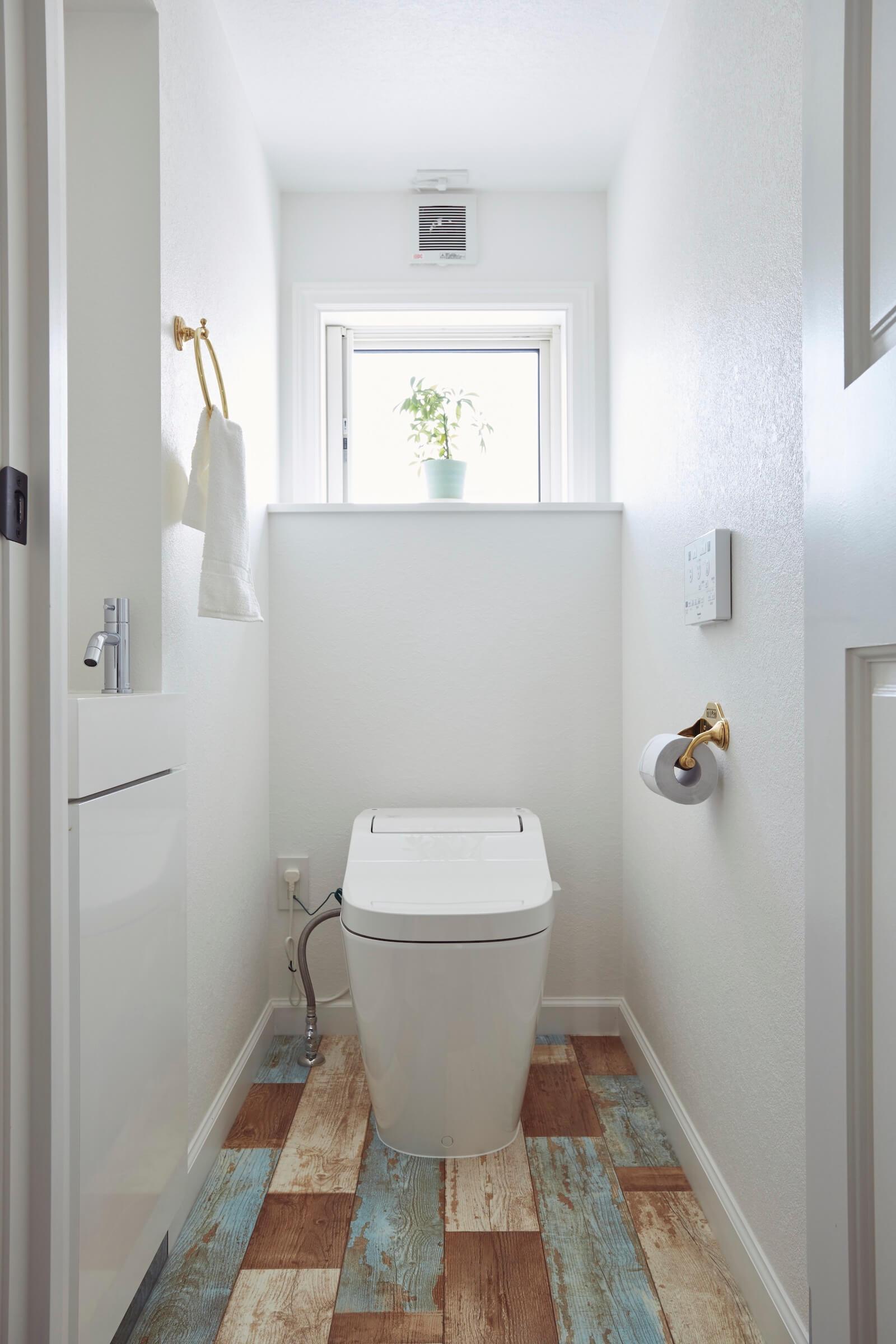 ビルトインガレージのアーリーアメリカンスタイルの輸入住宅のトイレ